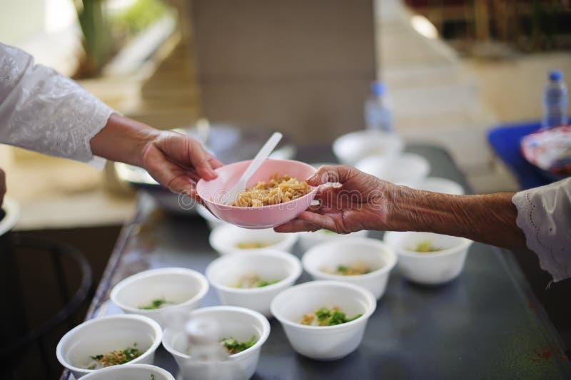 Sociala problem av armod som hj?lps, genom att mata: Volont?r att mata det hungrigt i samh?lle: Begreppet av att donera mat till  royaltyfri bild