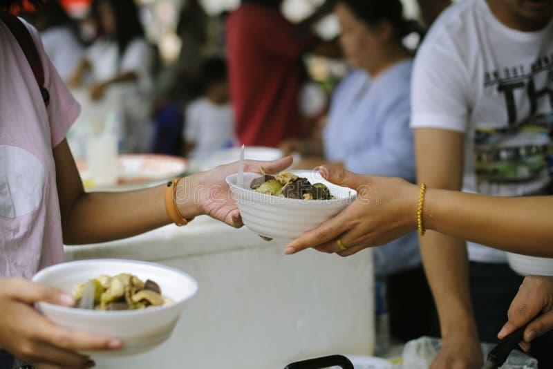 Sociala problem av armod som hj?lps, genom att mata: Volont?r att mata det hungrigt i samh?lle: Begreppet av att donera mat till  arkivfoto