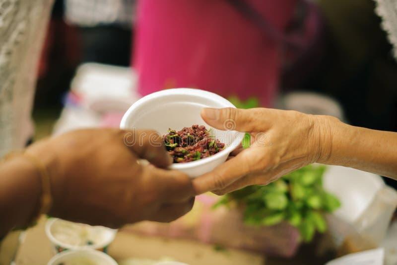 Sociala problem av armod som hj?lps, genom att mata: Volont?r att mata det hungrigt i samh?lle: Begreppet av att donera mat till  royaltyfria bilder