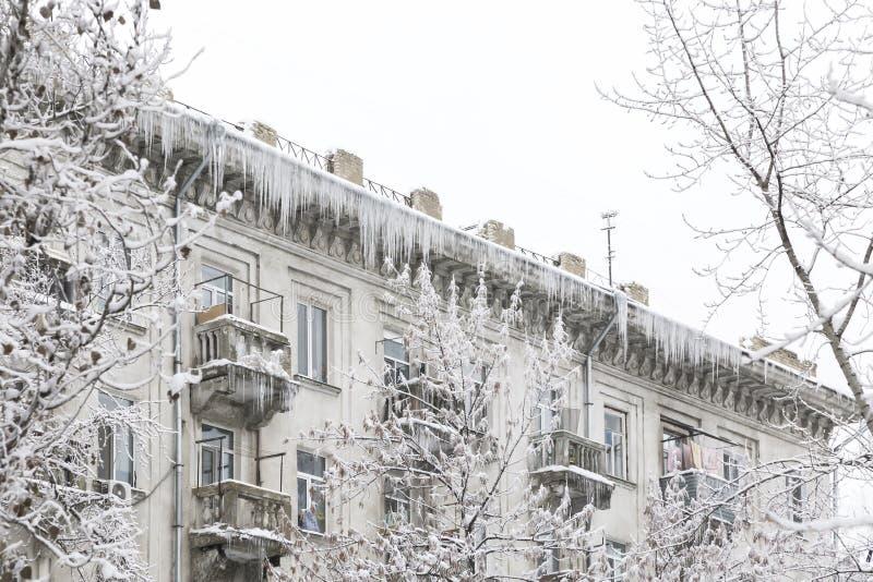 Sociala problem, uncleaned tak Vintersnöcityscape Enorma istappar hänger från taket av byggnaden som skapar faran av arkivfoton