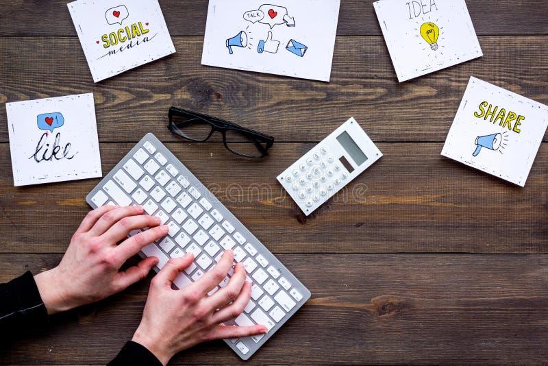 Sociale media bevordering Het werkbureau met socailmedia pictogrammen Donkere houten hoogste mening als achtergrond De hand typt stock foto