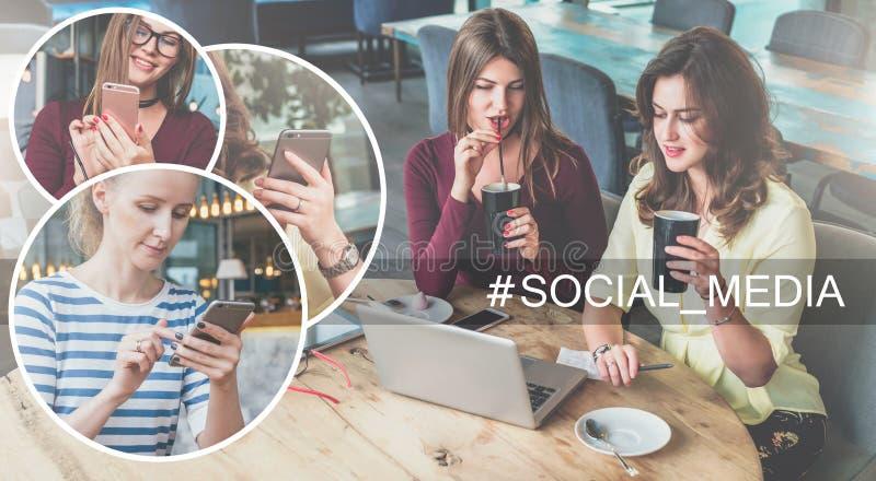 Sociale Media Twee jonge vrouwen die bij lijst in koffie, het drinken koffie zitten en het gebruiken van laptop stock foto's