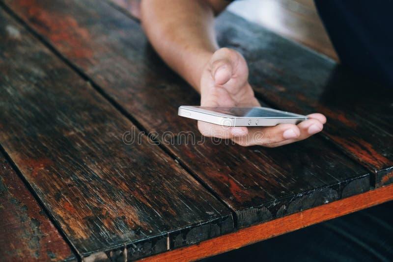 sociale netwerkmens, die op smartphonevertoning betrekking hebben, die smartphone houden stock fotografie