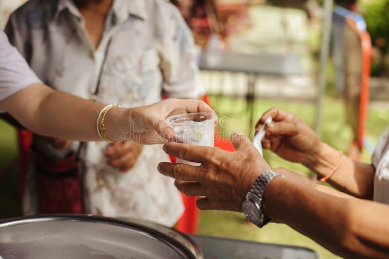 Socialt begrepp av fattigt dela för folk: Begrepp som tjänar som fri mat till det fattigt: Fri mat, genom att använda rester för  arkivfoton