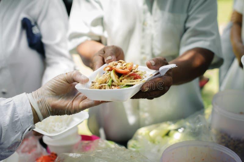 Socialt begrepp av fattigt dela för folk: Begrepp som tjänar som fri mat till det fattigt: Fri mat, genom att använda rester för  arkivbilder