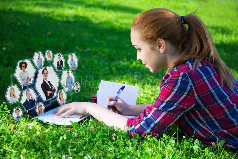 Socialt nätverksbegrepp - den tonårs- flickan som ligger på gräsplan parkerar in, och fotografering för bildbyråer