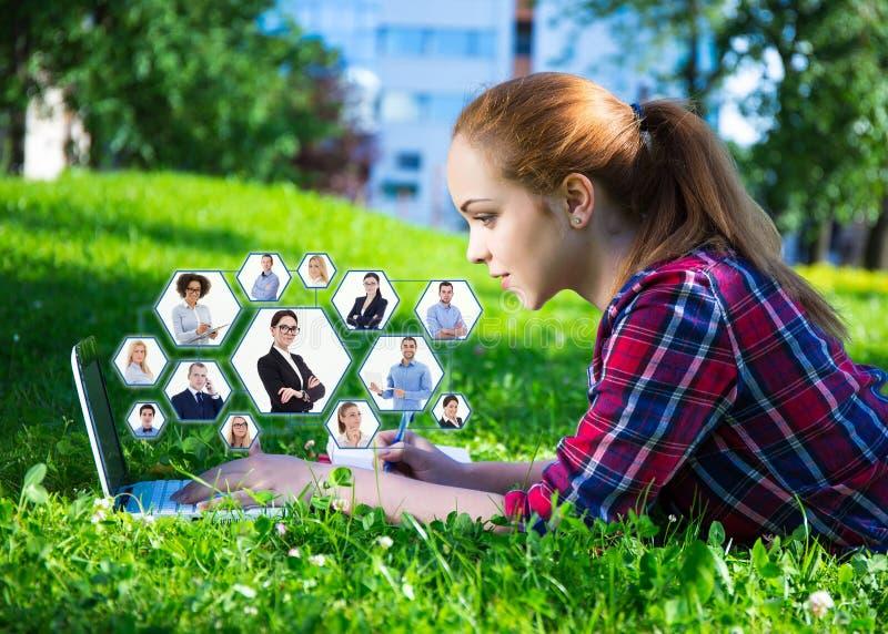 Socialt nätverksbegrepp - den tonårs- flickan som in ligger, parkerar med bärbara datorn royaltyfri fotografi