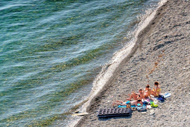 Società dell'uomo e di 3 giovani donne caucasiche in bikini che si abbronzano e che si rilassano sulla spiaggia pietrosa della co immagine stock