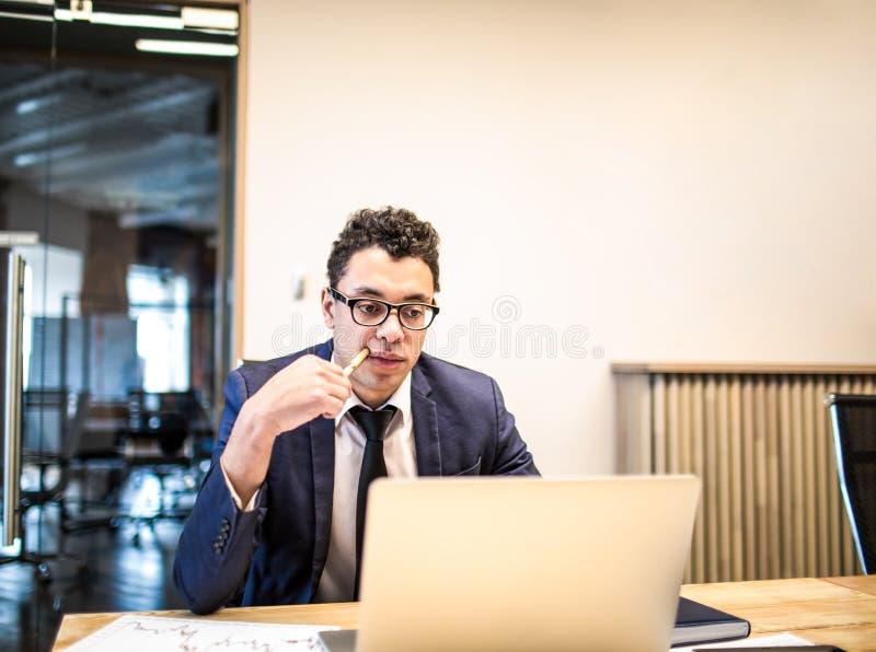 Società finanziaria del riuscito proprietario dell'uomo che lavora al computer portatile che si siede nell'ufficio immagini stock libere da diritti