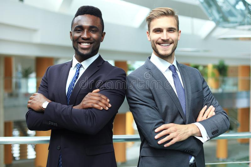 Socios comerciales afroamericanos y caucásicos que se unen de nuevo a la parte posterior y que miran in camera, en oficina foto de archivo