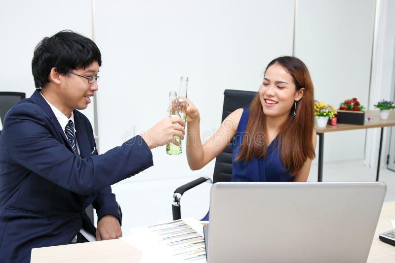 Socios comerciales asi?ticos jovenes alegres que tintinean la botella de vino en oficina Concepto acertado y de la celebraci?n imagen de archivo libre de regalías