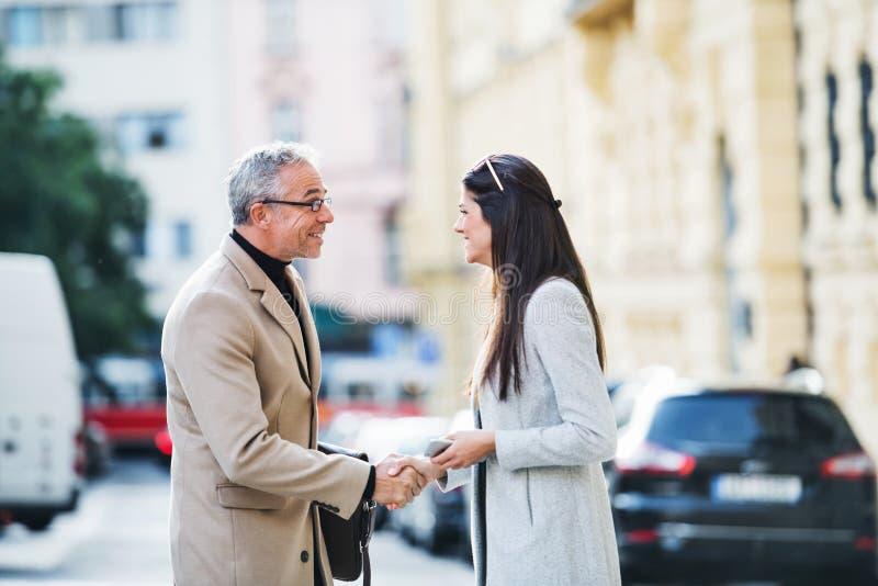 Socios comerciales del hombre y de la mujer que se colocan al aire libre en la ciudad de Praga, sacudiendo las manos foto de archivo