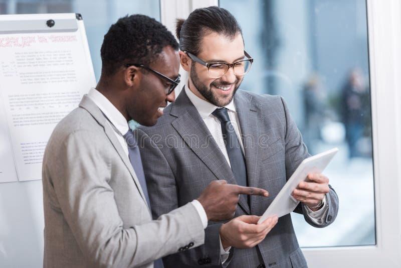 socios comerciales multiétnicos que miran la tableta digital imagenes de archivo