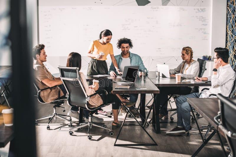 socios comerciales multiétnicos que tienen reunión en la tabla con los ordenadores portátiles en moderno imágenes de archivo libres de regalías