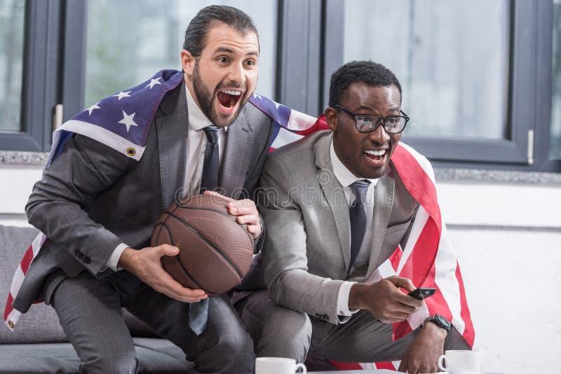 socios comerciales multiculturales felices con el partido de baloncesto de observación de la bandera americana foto de archivo libre de regalías