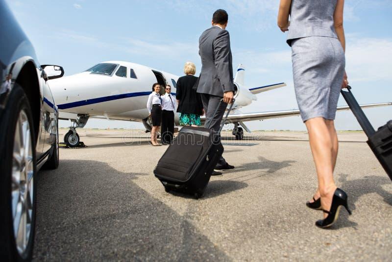 Socios comerciales que caminan hacia el jet privado imágenes de archivo libres de regalías