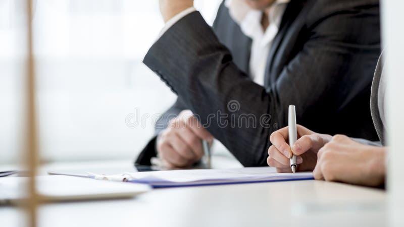 Socios comerciales que comprueban un documento mientras que lo firma imágenes de archivo libres de regalías