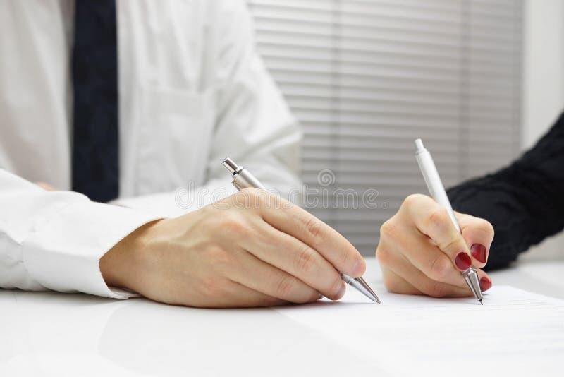 Socios comerciales que firman un documento foto de archivo