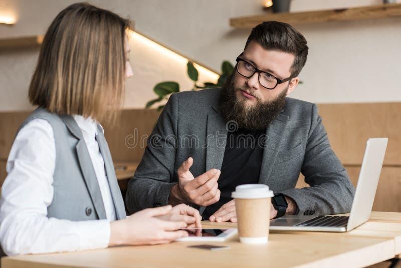 socios comerciales que tienen conversación en café moderno con los dispositivos y el café imágenes de archivo libres de regalías
