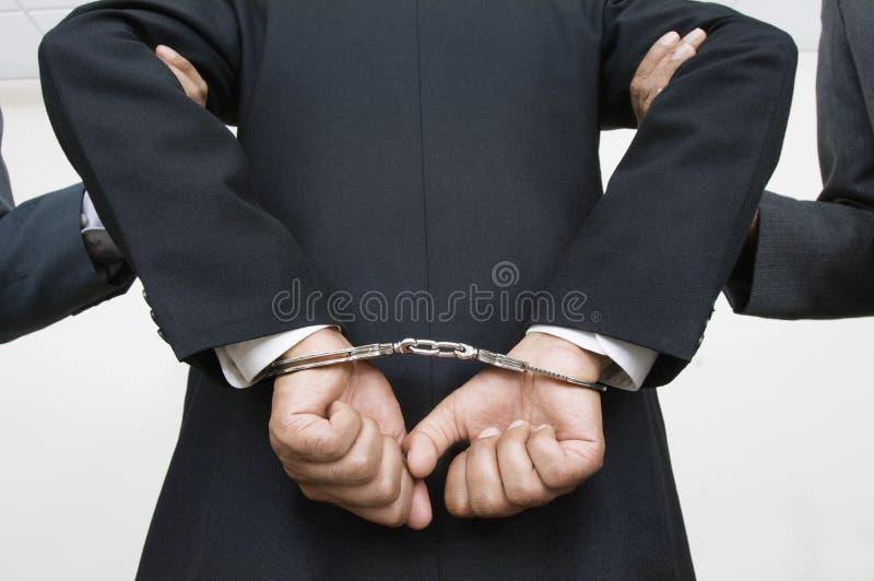 Socios de With Handcuffs While del hombre de negocios que se sostienen los brazos imágenes de archivo libres de regalías