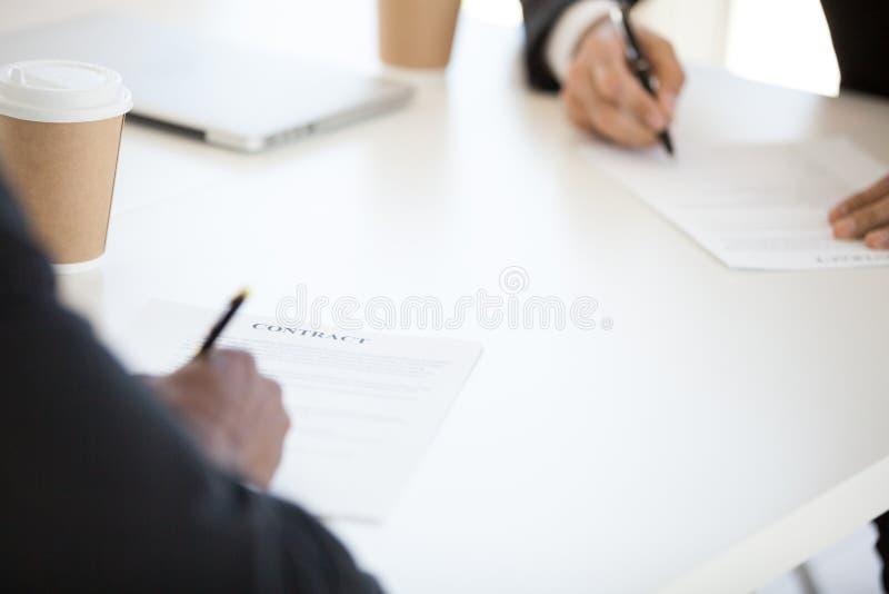 Socios que firman el contrato, cierre encima del foco en el documento imagenes de archivo