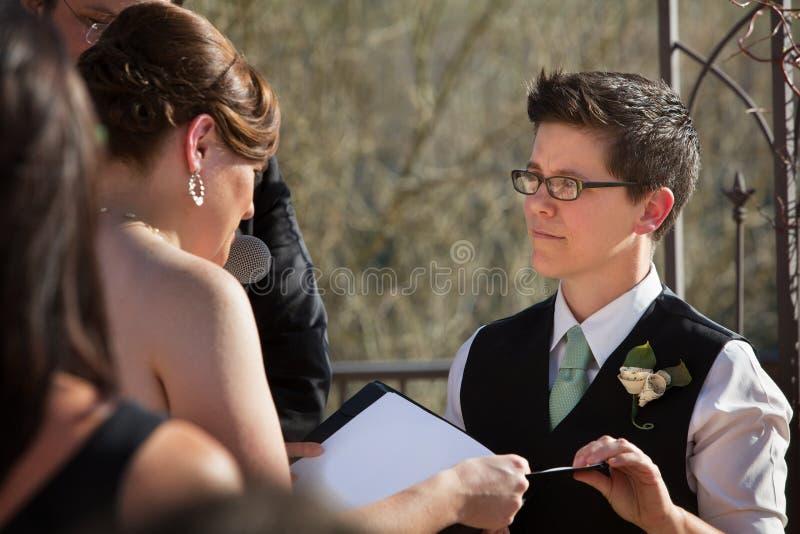 Socios que leen votos de boda fotos de archivo