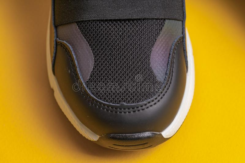 Sock black childrens school sneakers with Velcro on a yellow background. Close, studio, closeup, copy, modern, covering, banner, light, technology, art, design stock photography