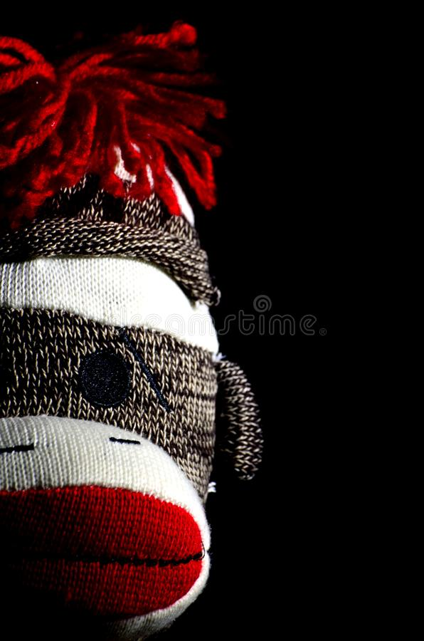 Sock Monkey Head is Watching. Practicing low key lighting with a classic toy, the sock monkey royalty free stock photography