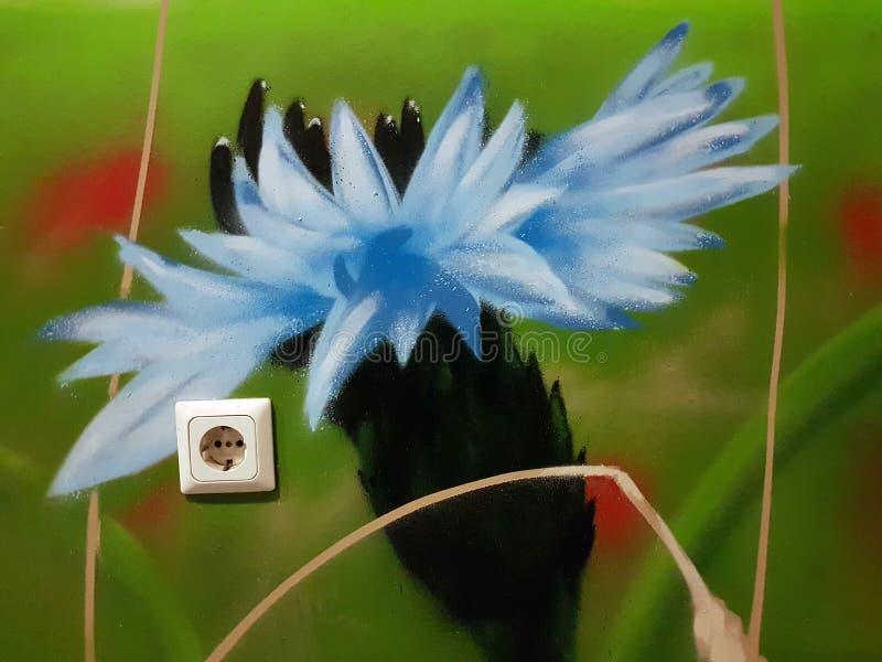 Sockel elektrisch in einer Hausmauer vor dem hintergrund der Blumengraffiti lizenzfreies stockfoto