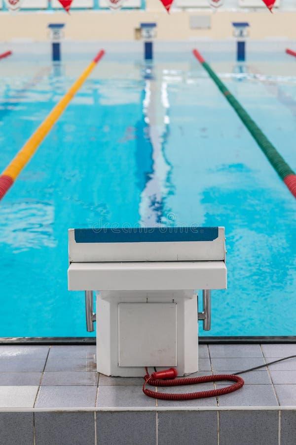 Sockel för simmare i den inomhus pölen med blått vatten och kulöra avdelare royaltyfri foto