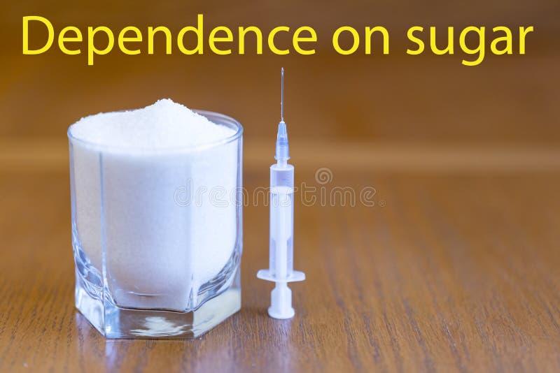 Socker och injektionsspruta begreppet av beroende på sötsaken socker jämförs med droger inskriftberoende på socker arkivfoton