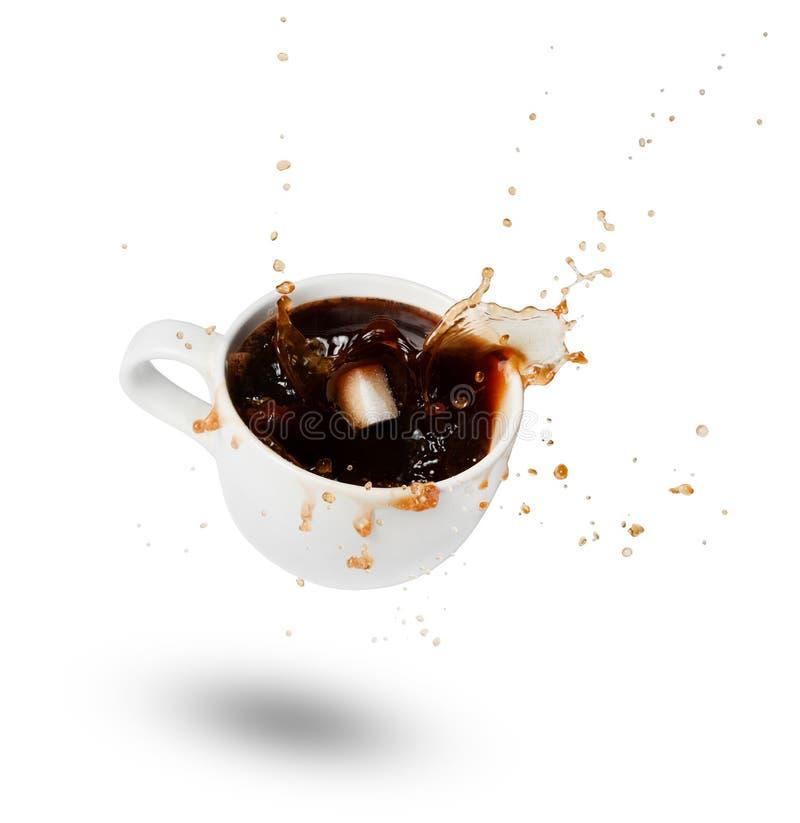Socker som faller in i en vit kopp kaffe bristningar Spridning av droppar uttryck Vit bakgrund arkivbild