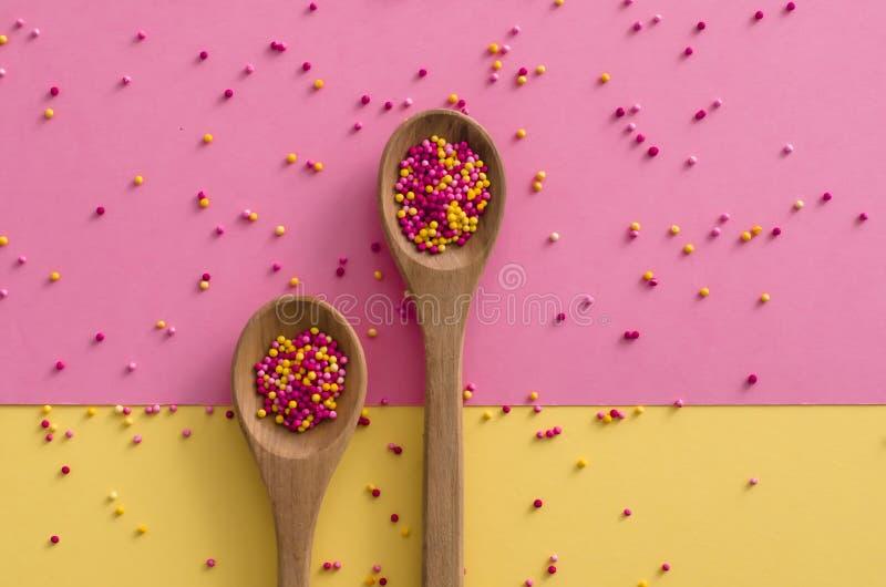 Socker strilar prickar i en träsked på rosa och gul bakgrund, garnering för kaka och bagerit royaltyfria bilder