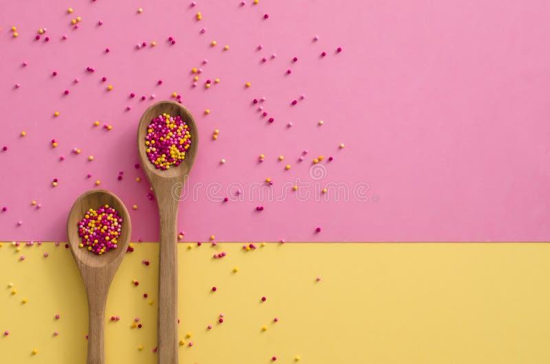 Socker strilar prickar i en träsked på rosa och gul bakgrund, garnering för kaka och bagerit arkivbild