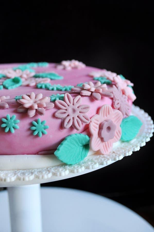 Sockerdeg blommar på den rosa tårtan royaltyfria foton