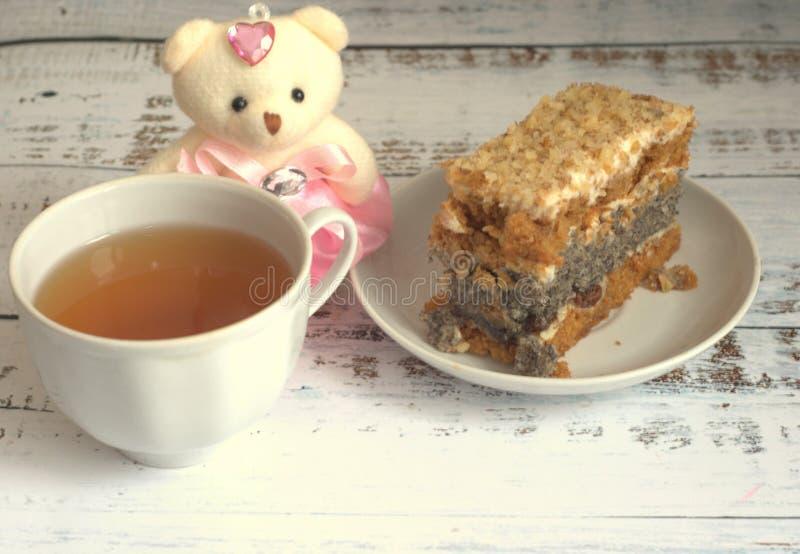Sockerkaka med vallmofrön på en platta, en kopp te och en nallebjörn som ligger på en trätabell royaltyfria foton