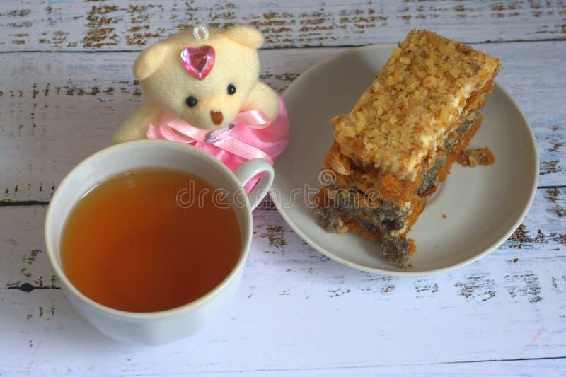 Sockerkaka med vallmofrön på en platta, en kopp te och en nallebjörn som ligger på en trätabell arkivbilder