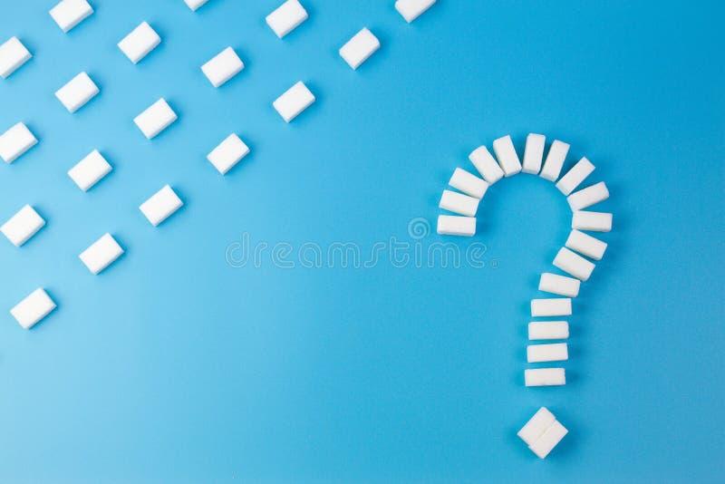 Sockerkuber som formas som en frågefläck, undertecknar på blå bakgrund arkivfoton