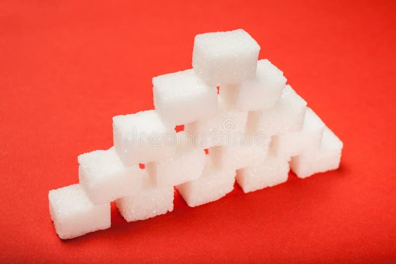 Sockerpyramid på en röd bakgrund royaltyfri fotografi