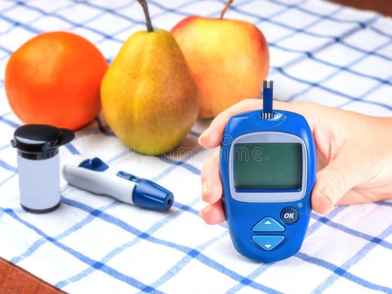 Sockersjuka som kontrollerar nivån för blodsocker Kvinna som hemma använder lancelet och glucometer royaltyfri fotografi
