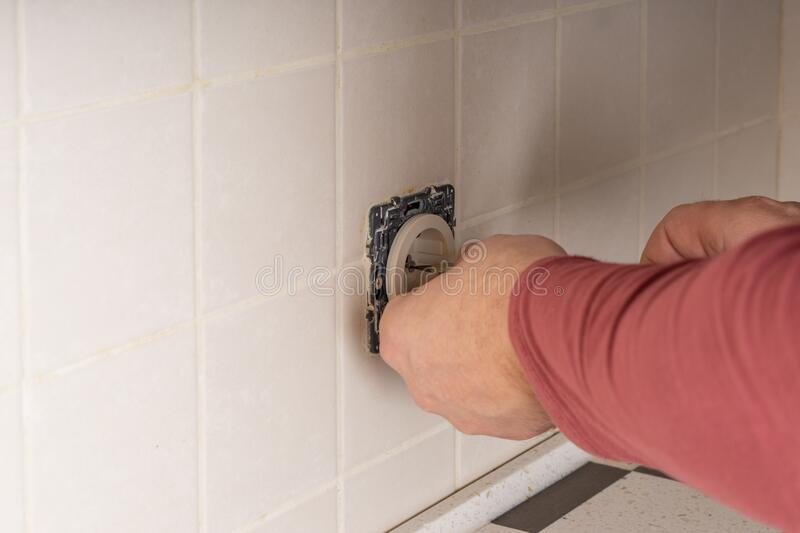 Socket Installation. A master electrician installs an electrical connector in a classic interior stock photo