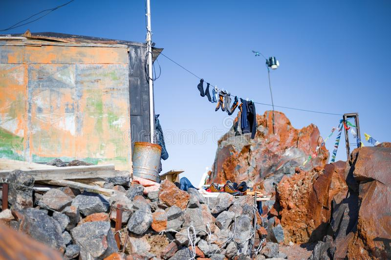 Socks and clothes of climbers drying on a rope high in the mountains near the old house royalty free stock photo
