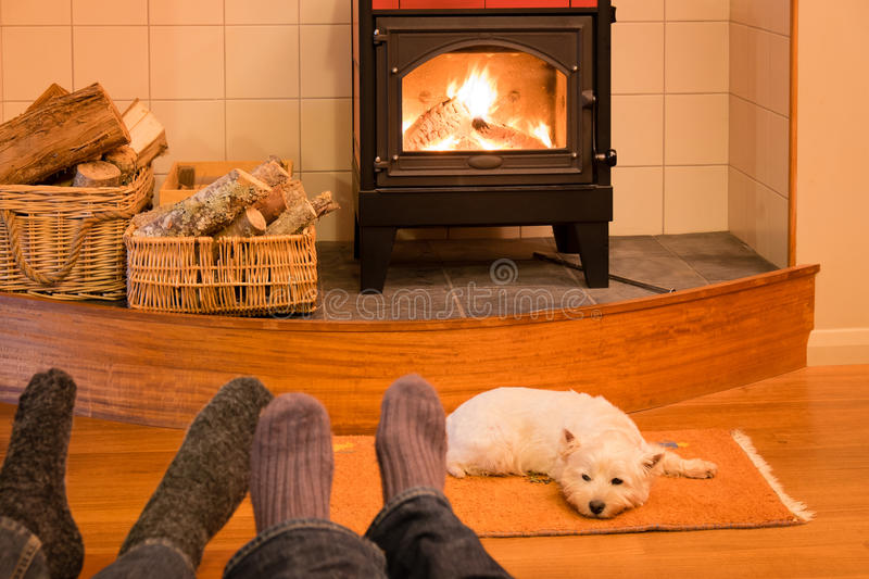Socks and feet of a couple relaxing by fire with west highland t. Socks and feet of a couple relaxing by fire in woodburner with west highland terrier - focus is stock photo