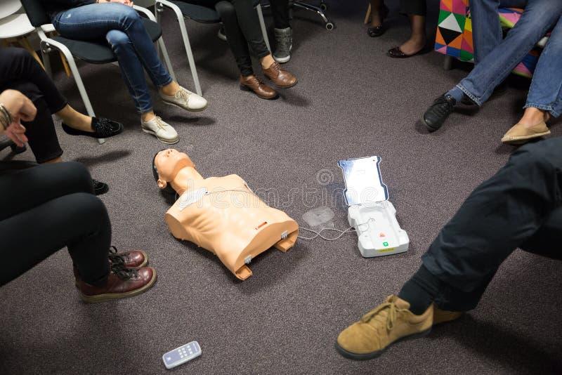 Socorros de ensino do instrutor primeiros curso da ressuscitação cardiopulmonar e uso do desfibrilador externo automatizado no CP fotografia de stock