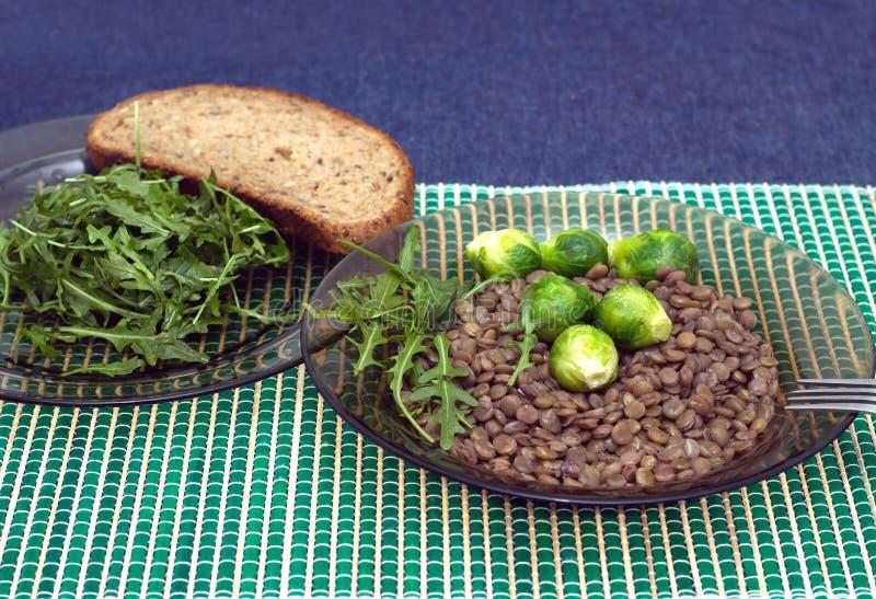 Soczewicy, brokuły i arugula sałatki liście z zbożowym chlebem na, talerze obraz royalty free