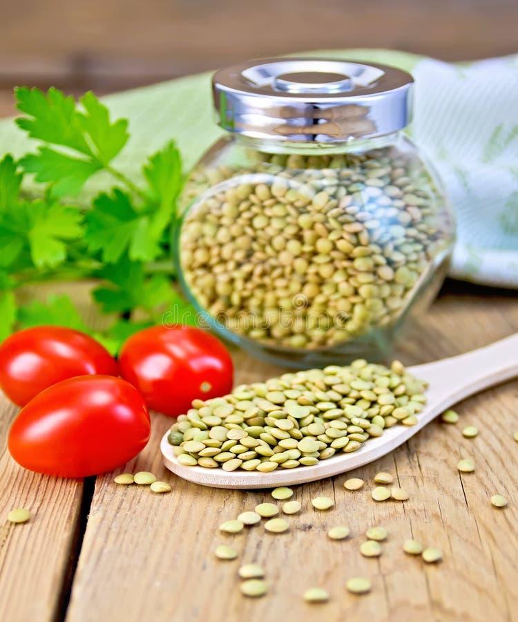 Soczewicy zielenieją w słoju i łyżce z pomidorami na pokładzie obraz stock