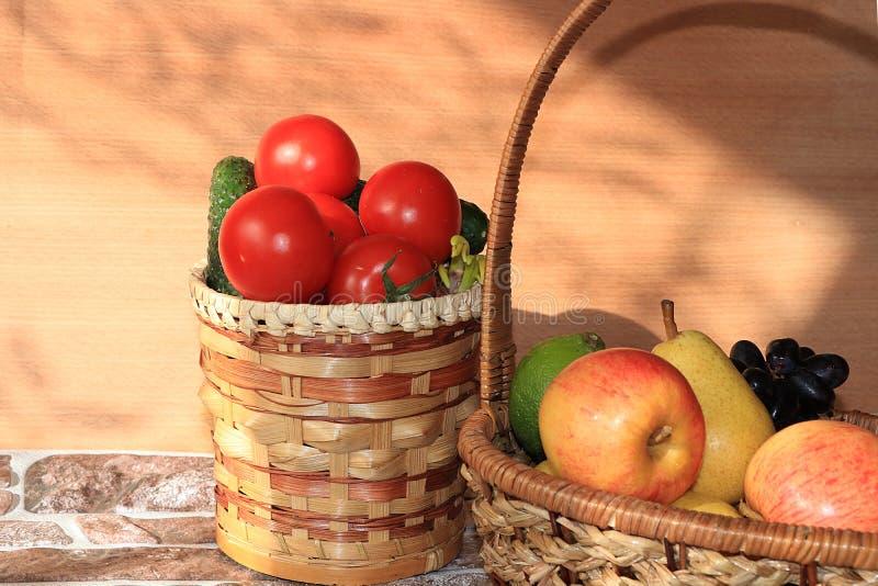 Soczyści czarni winogrona, jabłka, bonkrety, pomidory w koszu na stole obraz royalty free