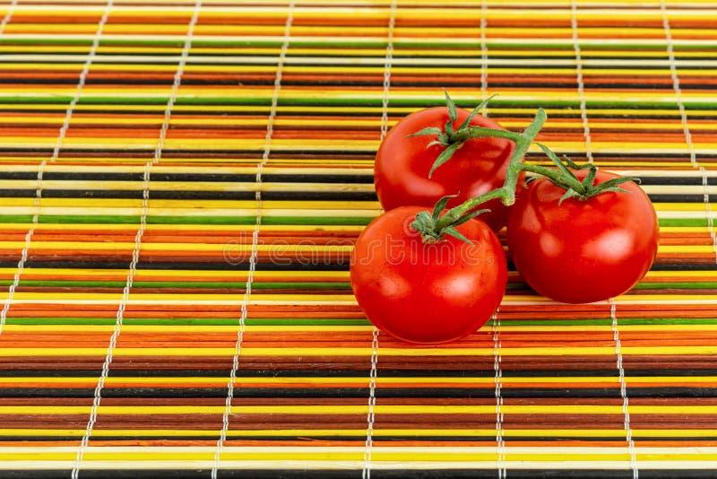 Soczyści jaskrawi czerwoni pomidory na zielenieją gałąź trzy warzywa na kolorowej bambus bazy pomarańcze zieleni żółtym czerni obraz royalty free