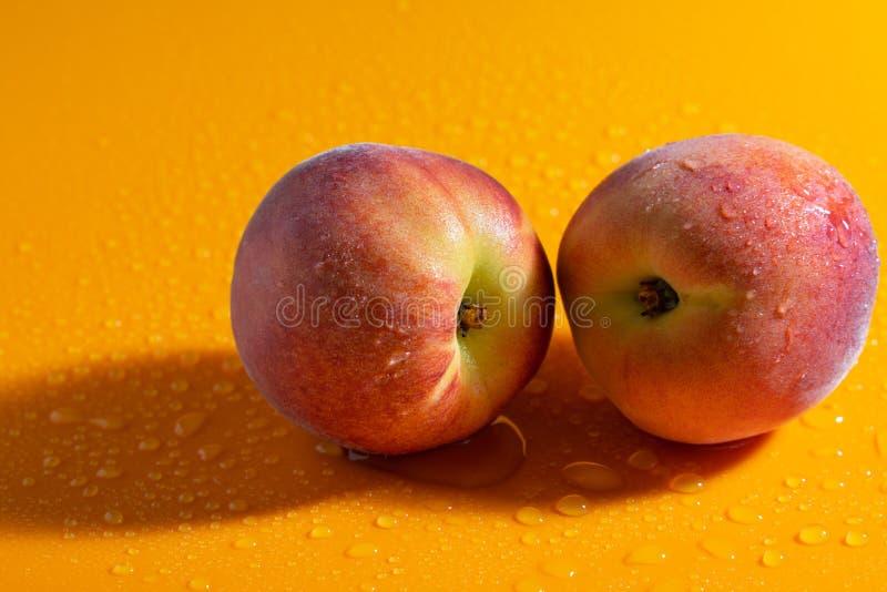 soczysta świeża dojrzała brzoskwinia na pomarańczowym matte tle z wodnymi kroplami owoc i zdrowy jedzenie zdjęcie stock