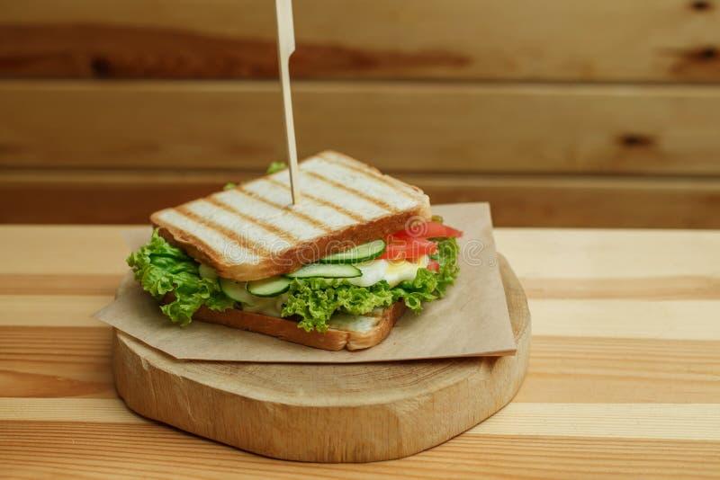 Soczysta kanapka z bekonem, świeżymi warzywami, zieloną sałatką i ciemnymi liniami po grilla na drewnianym talerzu, zdjęcia stock